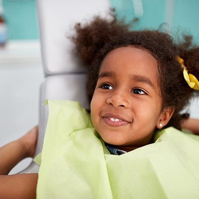 Young girl smiling dental chair for their first visit